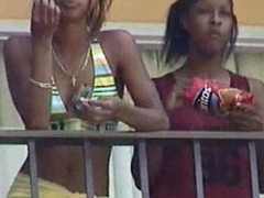Black lesbians giving a kiss on hotel balcony